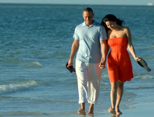 两夫妻拿着鞋在海滩上走实拍片段